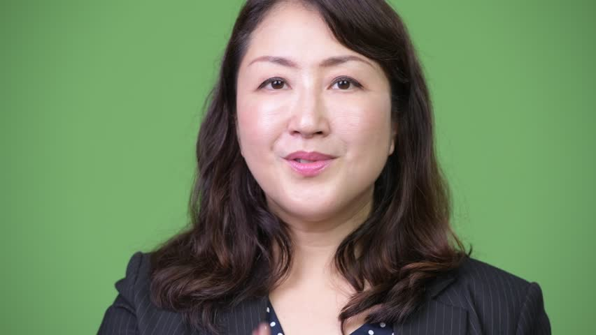 Mature beautiful Asian businesswoman with finger on lips | Shutterstock HD Video #1013378927