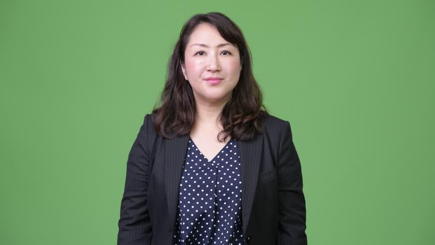 Mature beautiful Asian businesswoman nodding head yes
