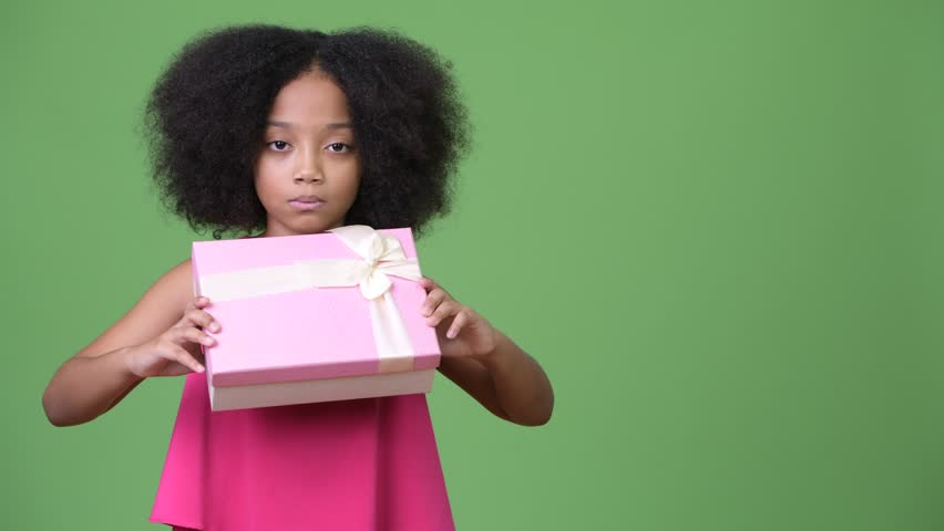 Young cute African girl with Afro hair holding gift box | Shutterstock HD Video #1013381330