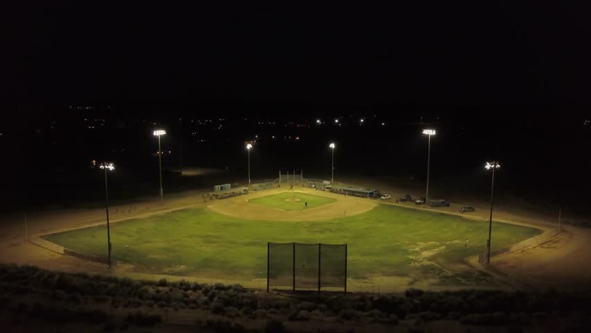 Aerial zoom out of a night time baseball game