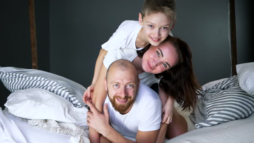 happy moments, young parents with son have fun together on bed at home in bedroom #1013387540