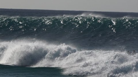 Surfers surfing massive waves. Big swell with huge waves hitting the north shore of Hawaii. Tubes, barrels and water tunnels are surfed by professional. Dangerous high waves at Banzai Pipeline Oahu