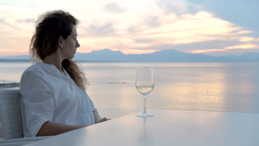 Woman sipping white wine and enjoying the view of a beautiful golden summertime sunset. | Shutterstock HD Video #1013396855