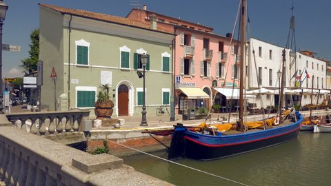 CESENATICO (FC), ITALY - JUNE 7, 2018: tourists are walking along moored boats of the Leonardesque canal port
