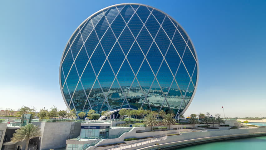 ABU DHABI, UAE - CIRCA MARCH 2018: Circular skyscraper Aldar Headquarters Building timelapse hyperlapse in Abu Dhabi, UAE. View from bridge. It is the first circular building of its kind in the Middle