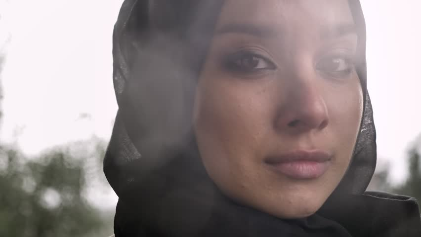 Portrait of young sad muslim woman in hijab looking at camera and crying, rainy weather in background