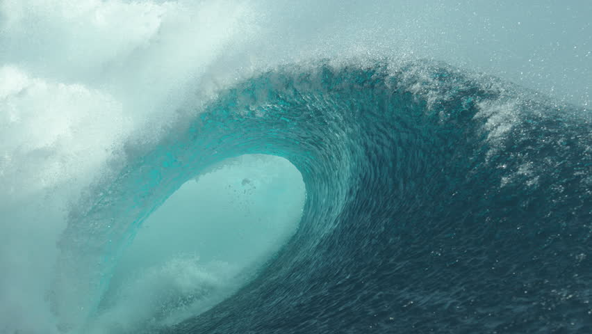 SLOW MOTION, CLOSE UP: Forceful barrel wave splashes beautiful crystal clear water everywhere around the sunny coast of Tahiti. Amazing shot of a large tube wave right when it breaks and crashes.