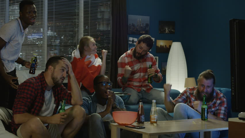 Diverse friends with Canadian flag watching game and celebrating victory of sport steam while chilling at home | Shutterstock HD Video #1013428283