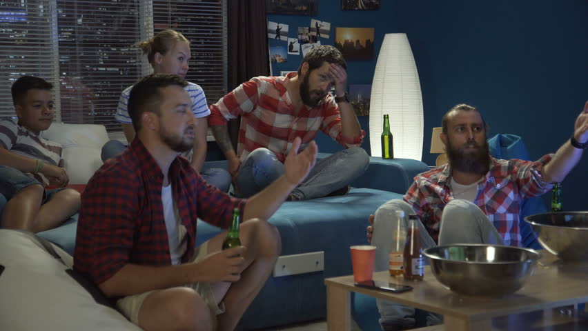 static shot of group of men and woman with teenager relaxing on couch at home having beer watching sport game #1013428298