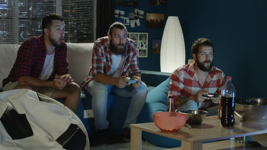 Group of man chilling on sofa with gamepad and man mocking on other player when winning videogame round and having fun tease him #1013428385