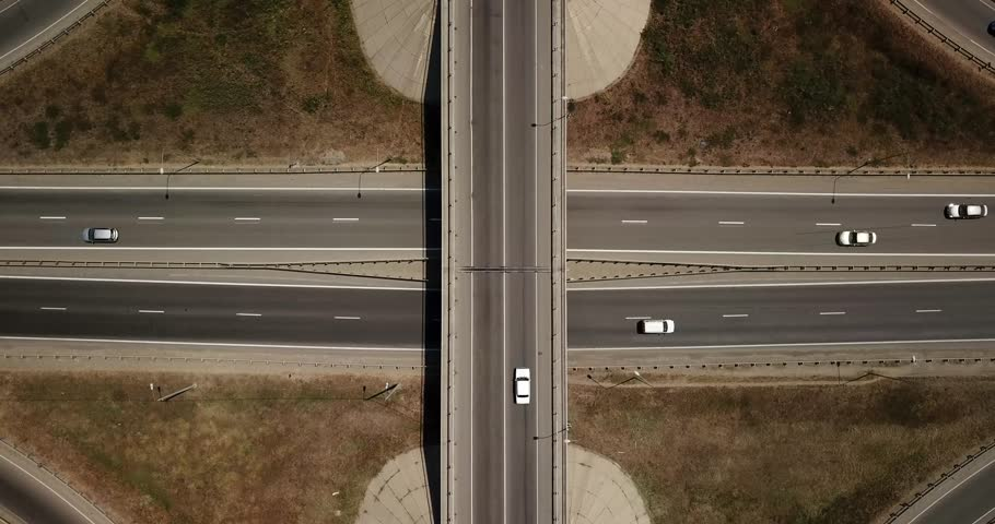 Summer aerial footage of transport junction, traffic cross road junction day view from above with circle road. Top down view of traffic jam.