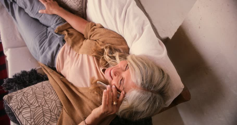 Mature woman lying down on sofa, relaxing and laughing while talking on mobile phone
