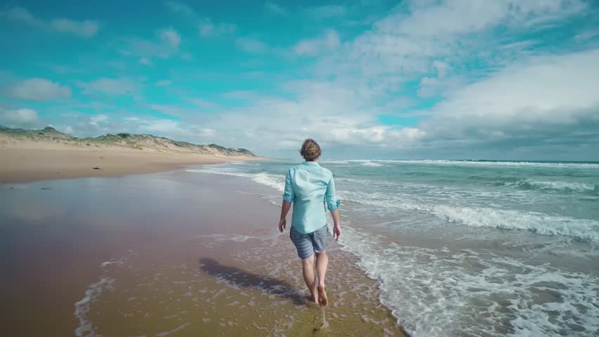 A tracking shot of a man walking along the shoreline of the ocean from behind.