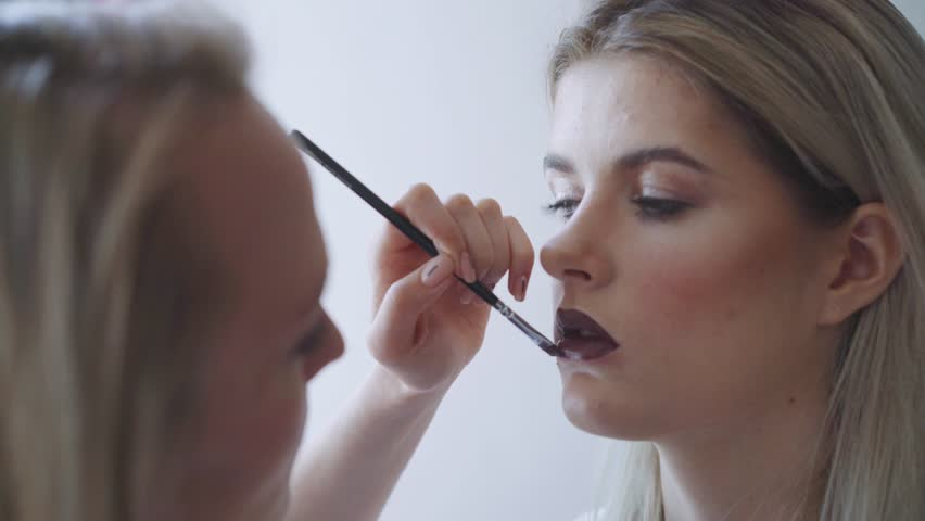 Portrait of a beautiful woman, lipstick paints a dark color, looking in the mirror. An attractive beautiful girl paints her lips with lipstick.
