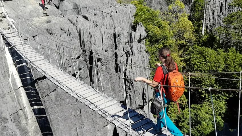 Tsingy de Bemaraha, MADAGASCAR - MAY 18, 2018: Hiker tourist walks over suspended rope bridge over gorge in national park