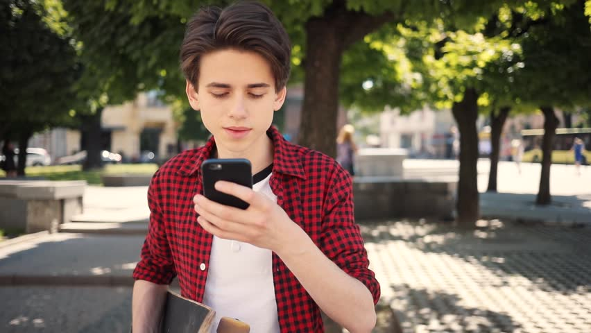 Attractive boy using a mobile phone smile walk keeps skate guy business fashion hand child sun man nature internet social smartphone lifestyle smart teenager young cell communication slow motion