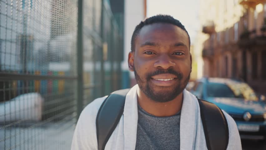Good-looking young man with backpacks on back looking at camera, smiling. Likable African guy wearing casual clothes looking directly at camera. Outside. | Shutterstock HD Video #1013464802
