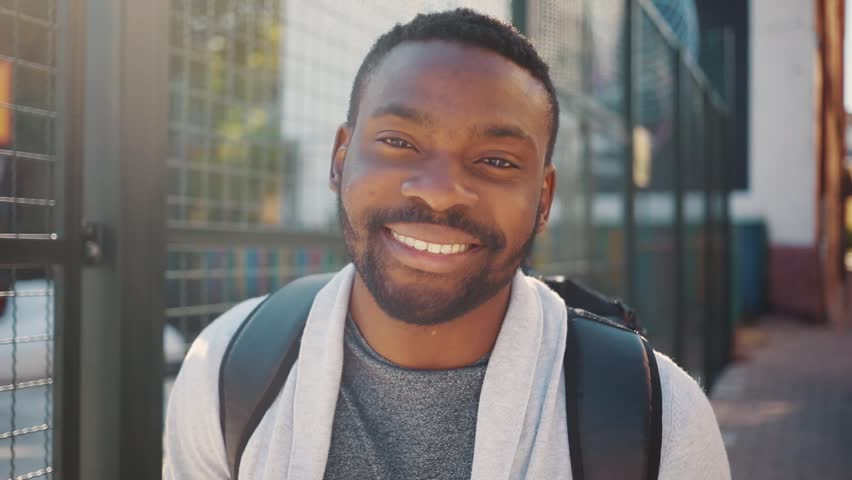 Handsome optimistic African student with beautiful smile looking directly at camera, smiling. Portrait of attractive young man on background of street. Outdoors. Summertime. | Shutterstock HD Video #1013464808