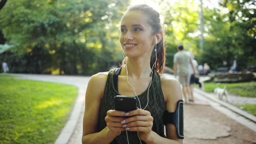 Happy young woman use smartphone and headphone standing in park sun outdoor health hand girl tree sport fitness summer nature internet technology female runner exercise phone workout mobile cellphone