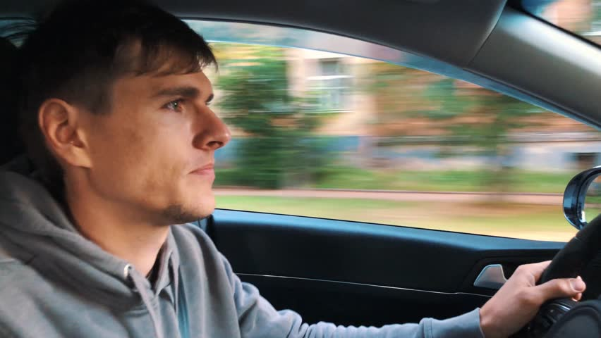 Handsome man driving a car, cityscape outside | Shutterstock HD Video #1013470277