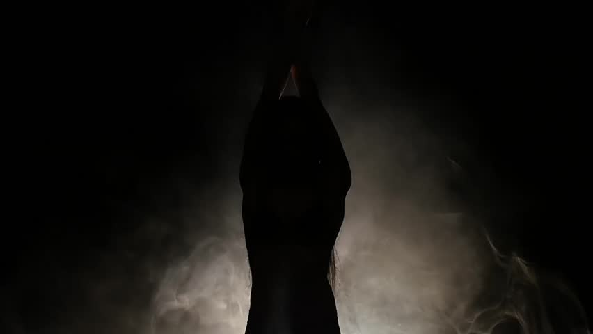 Girl is dancing a sexy dance . Black background. Silhouette. Slow motion