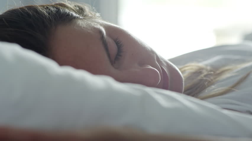Close up face of young Caucasian woman lying and stretching on bed after waking up early in the morning #1013510528