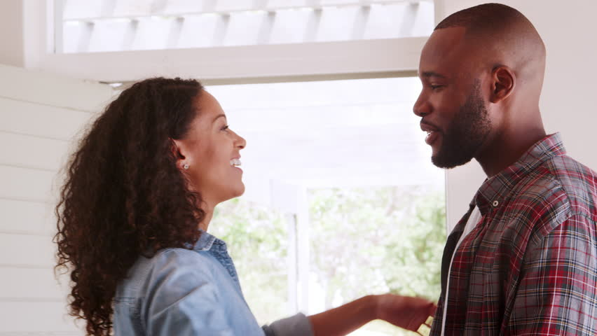 Loving Couple Hugging By Door Of New Home