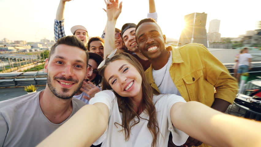 Attractive young woman is taking selfie with friends on rooftop, girl is holding camera and posing while her mates are having fun making funny faces and gestures. #1013525267