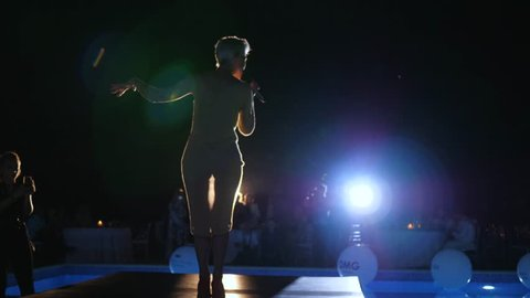 Kherson, Ukraine 02 June 2018: singer female with microphone in hand on stage with musicians makes concert performance in Kherson, 02 June 2018.