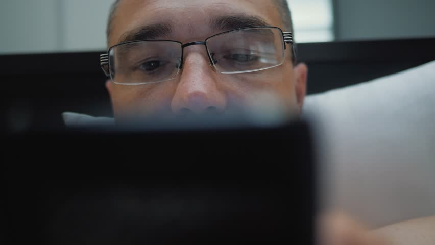 A man lying on a bed wearing glasses communicates on a smartphone | Shutterstock HD Video #1013534033