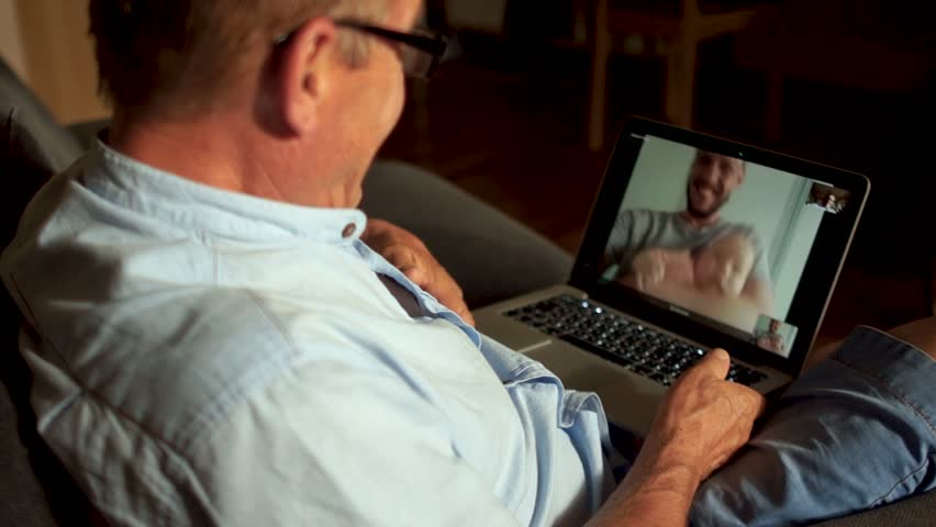 A mature man talks to his adult son and newborn grandson on Skype. Video communication, three generations of one family