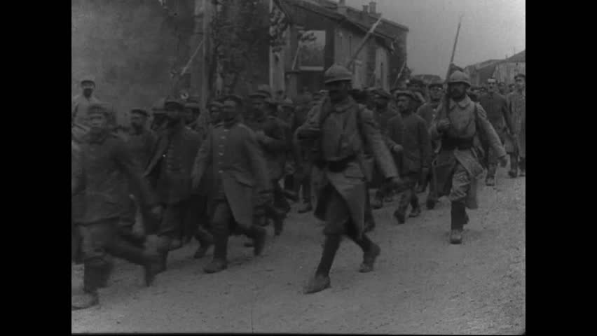 CIRCA 1916 - French soldiers march thousands of German POWs - infantrymen and officers - through a French town.