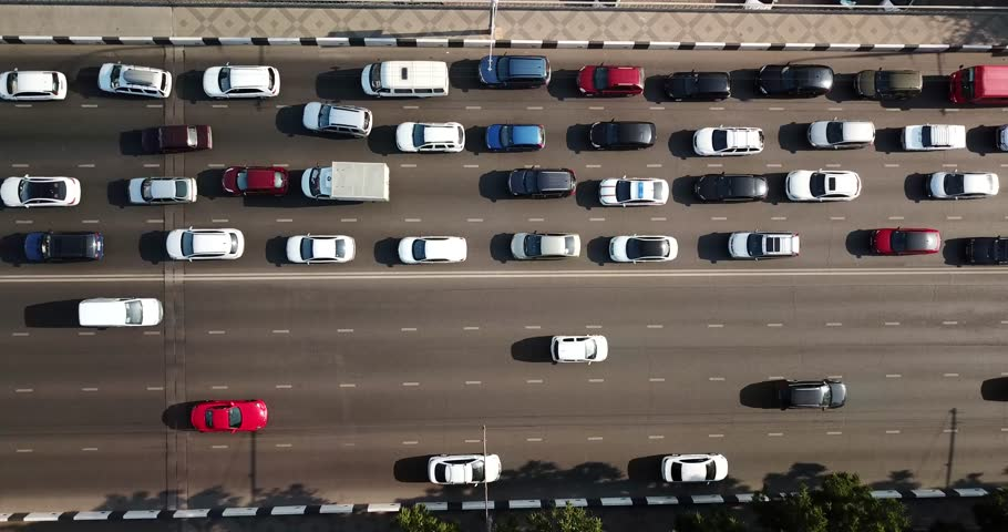 Aerial Drone Flight top down View of freeway busy city rush hour heavy traffic jam highway.  Aerial view of the vehicular intersection,  traffic at peak hour with cars on the road, over the bridge.