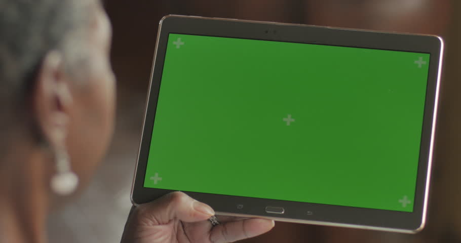 Happy senior black woman in her 50s or 60s using technology, swiping and tapping a green screen digital tablet - OTS | Shutterstock HD Video #1013549069