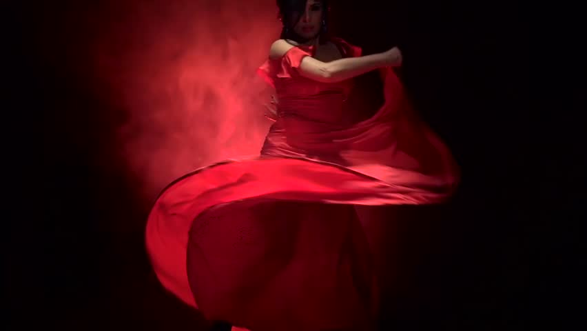 Dancer in a chic dress turns in an incendiary dance of Argentine flamenco . Llight from behind. Smoke background. Slow motion