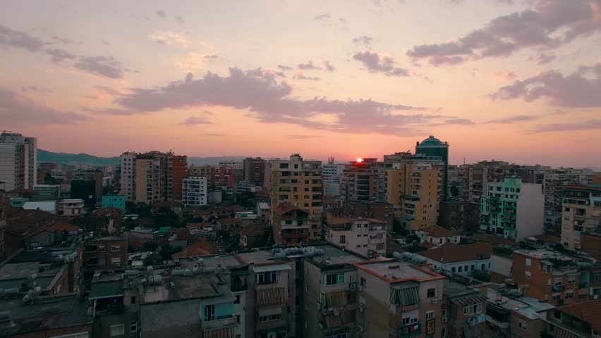 Aerial drone shot rising above the city of Tirana, Albania as a dim red sun sets along the horizon
