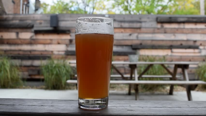 Slow pan of an amber colored beer on a summer day. Outside on the patio with greenery in the background. Ice cold beer!