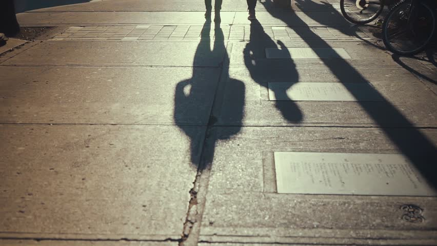 The evening sun casts shadows of two people walking down Queen Street West in Toronto SLOW MOTION