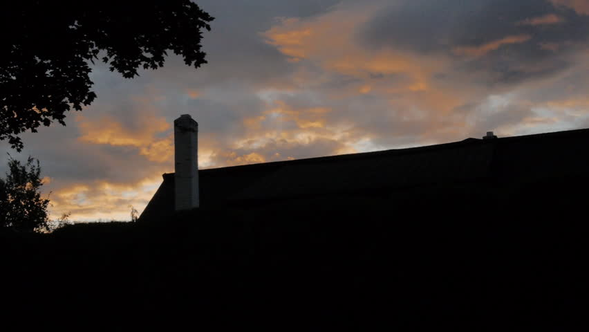 Slow Motion Moving Past Sunset Clouds Over House With Chimney