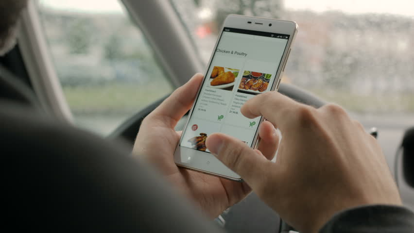 A man looks at the smoked chicken goods in the online grocery store, sitting in the car. Smartphone online shopping smoked delicacy. New York, June - 2018 | Shutterstock HD Video #1013591474