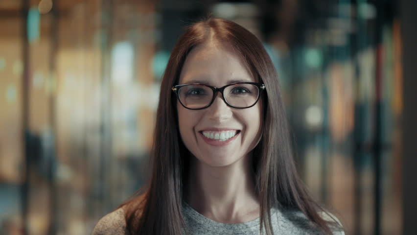 Portrait of attractive smiling young woman in glasses close up face of happy brunette female with long hair in good mood casual team leader or businesswoman in modern start up office positive emotions