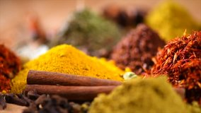 Spices. Various Indian Spices on wooden table. Spice and herbs rotated on wood background. Assortment of Seasonings, condiments. Cooking ingredients, flavor. Slow motion 4K UHD video
