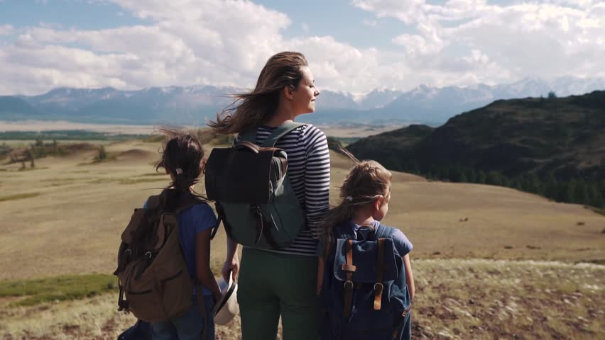 Family of tourists on a journey. mother with two daughters in the campaign. children with backpacks admire the view of the mountains | Shutterstock HD Video #1013629178