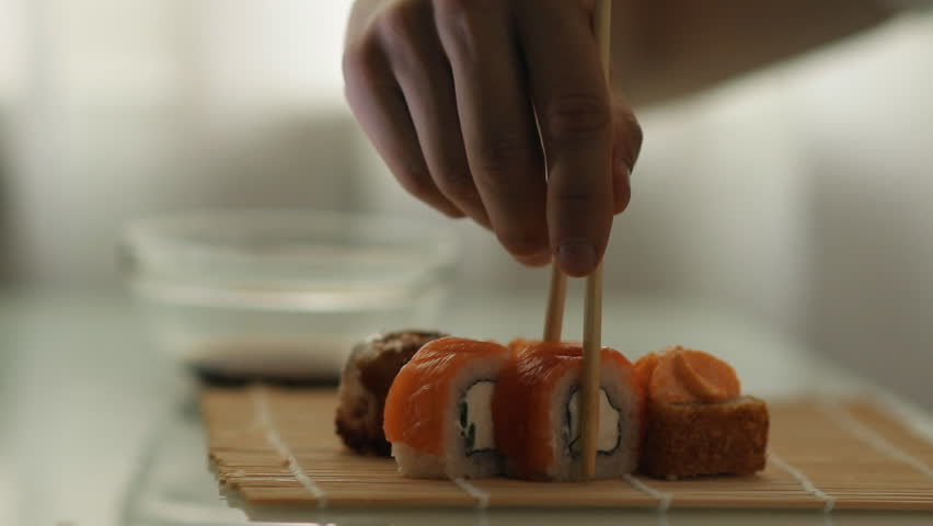 Lunch at a Japanese restaurant. Man eating sushi.
