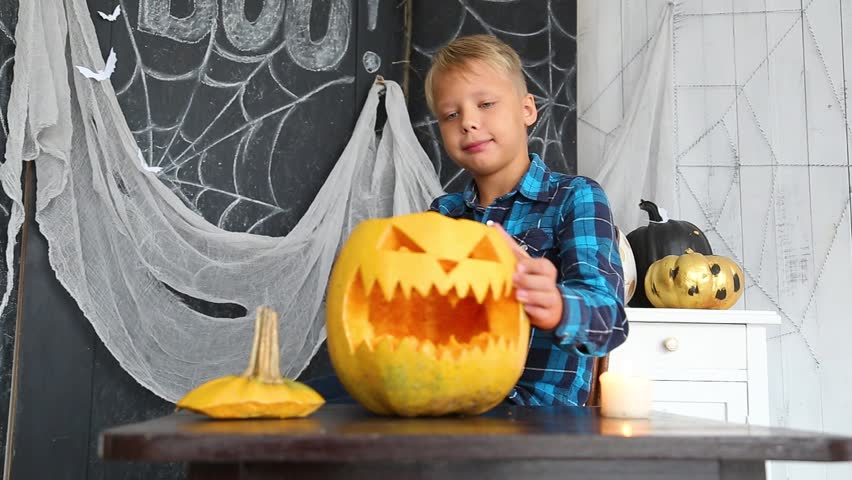 Young boy cutting scary face in pumpkin for Halloween celebration. | Shutterstock HD Video #1013639519