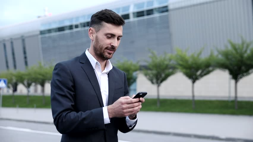 Portrait in Profile of Handsome Office Worker Walking in the City. Typing a Message on his Smartphone. Looking with smile at Phone Screen. Chatting on Social Media. Networks. Royalty-Free Stock Footage #1013642138