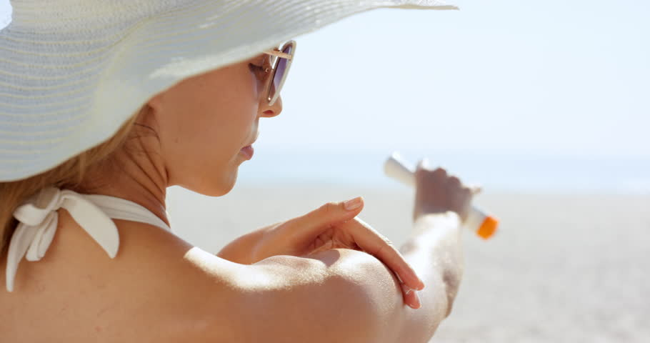 Close up of woman applying sunscreen to shoulder on tropical beach wearing one piece white bathing suite and white hat RED DRAGON