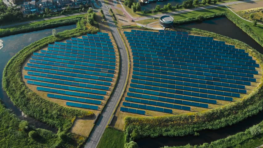 Aerial shot of a a solar panel farm with a road in the middle revealing modern suburban city district that is powered by the solar panel array. Almere, The Netherlands. Royalty-Free Stock Footage #1013657270