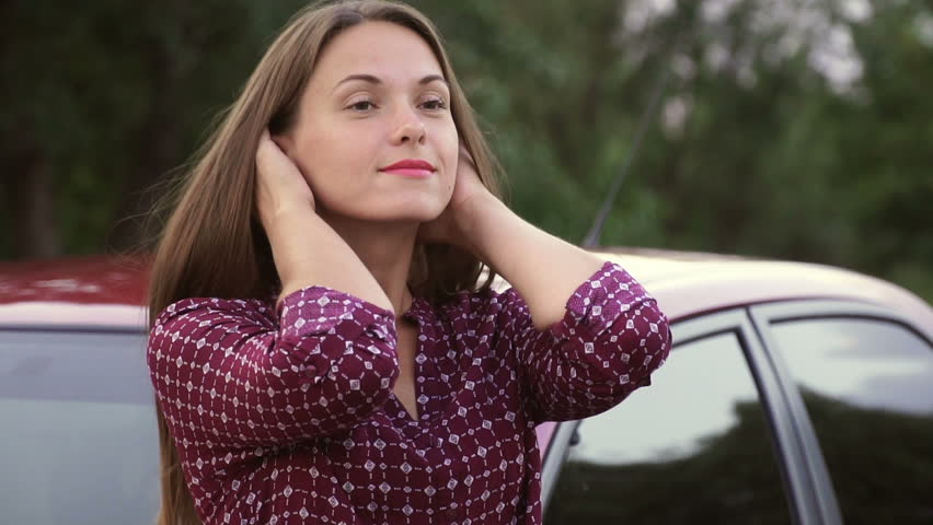 A sweet girl straightens her hair against a red car | Shutterstock HD Video #1013666426