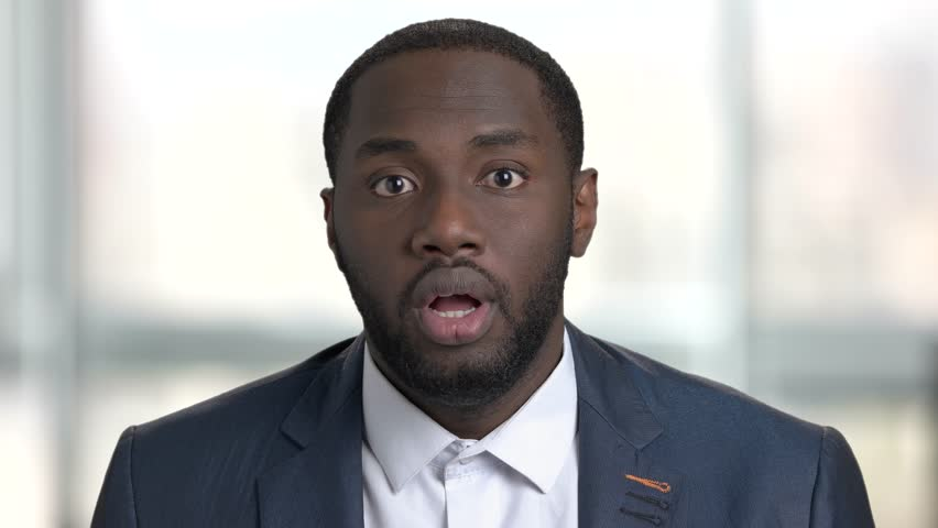Portrait of shocked afro american business man. Surprised and shocked face of black man in suit, close up. Bright office, windows background. | Shutterstock HD Video #1013667344